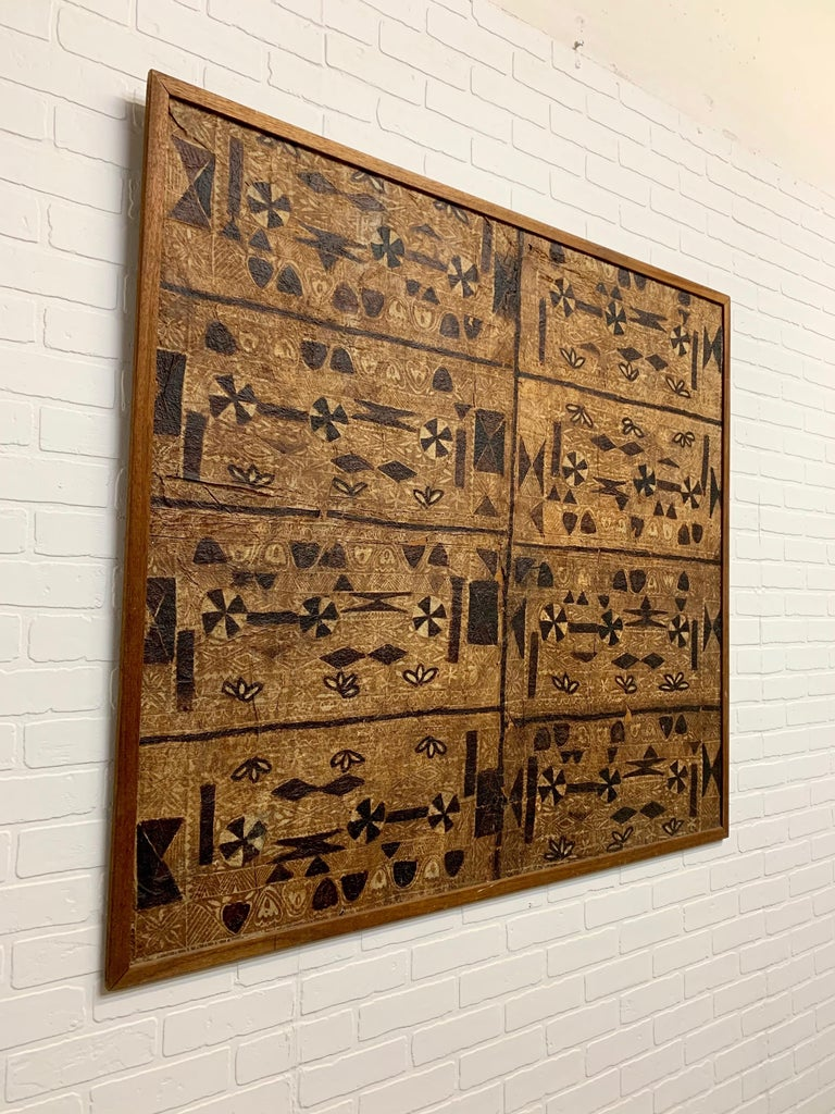 Bark cloth or tapa cloth mounted on plywood and trimmed in mahogany.  Bark cloth, or tapa, is not a woven material, but made from bark that has been softened through a process of soaking and beating. The inner bark is taken from several types of