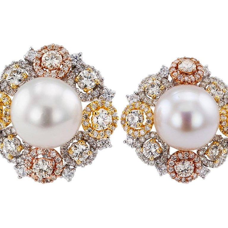 South Sea button pearl diamond gold ear clips. Showcasing a pair of  South Sea button pearls measuring 11.65 mm, within a diamond border comprising eight round diamonds set at equal intervals, in turn, each inside its own diamond halo, the color of