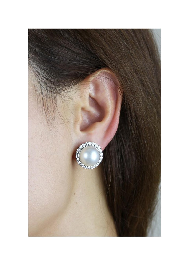 Elegant pearl and diamond earrings set in 18 carat white gold. Formatting of a singular powerful, perfectly round, pearl in the centre and surrounded by round brilliant cut diamonds. A statement jewellery embracing modern pizzazz and vintage classy