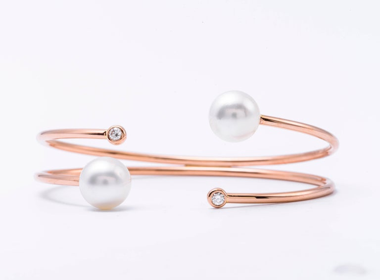 18K Rose gold bangle bracelet featuring two South Sea Pearls measuring 9.50-10 mm each and 2 round brilliants weighing 0.12 carats.  Color G-H Clarity SI  Pearls can be changed to Pink, Tahitian or Golden upon request. Price subject to change.