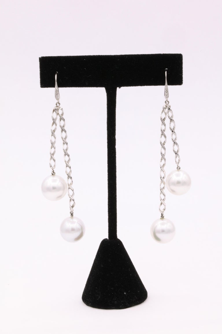 14K White gold swirl earrings featuring 8 round diamonds weighing 0.10 carats and four South Sea pearls measuring 12 mm.  Can be worn day or night!