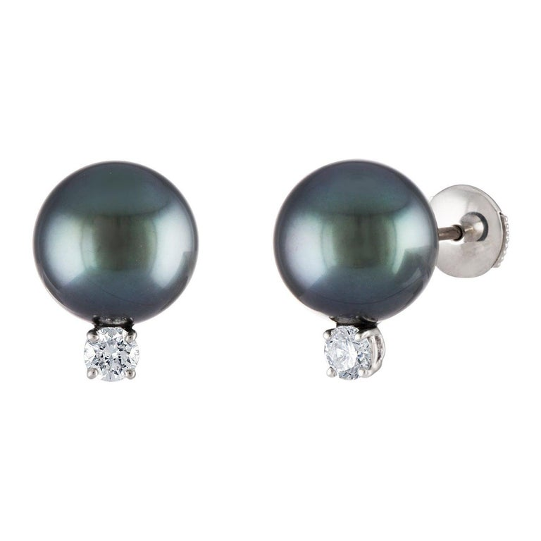 These classic South Sea Tahitian pearl earrings feature round 10.5mm pearls atop 0.20 total carats of diamonds. The earrings are set on 14 karat white gold.  Perfect for weddings, anniversaries, birthdays and graduations. Symbolizing purity and