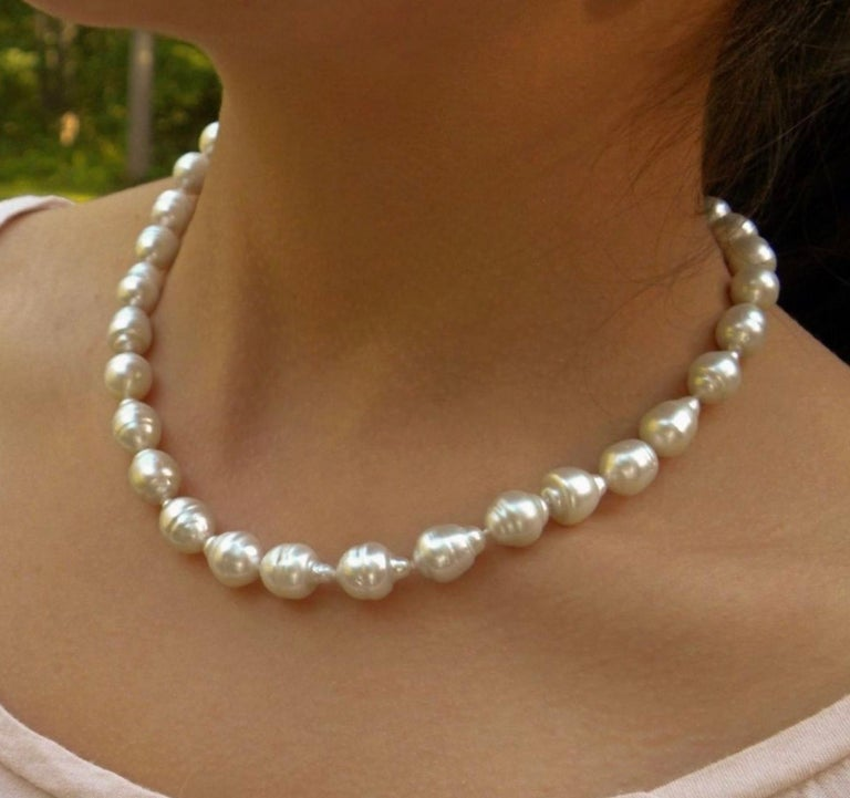 A necklace featuring graduated south sea white cultured baroque pearls ranging from 11.00mm-14.85mm. Deep Thick Nacre ~ Natural Color with 14k gold clasp. The necklace is 17.5