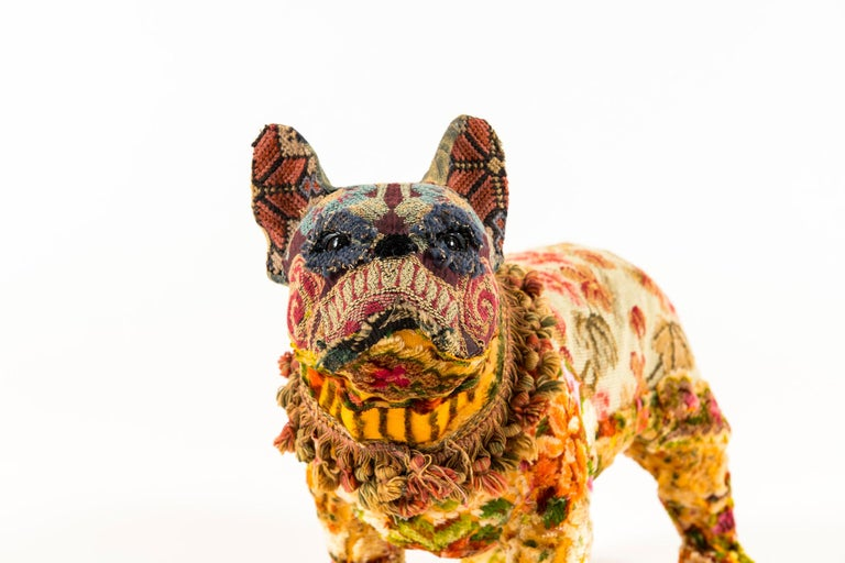Maxie is flower embellished bull dog with a mix of bright textiles to include: 1940s floral needlepoint body; vintage cut chenille on underbody neck, and legs; vintage embroidery from costume on Maxie's face; antique fringe trim collar and face