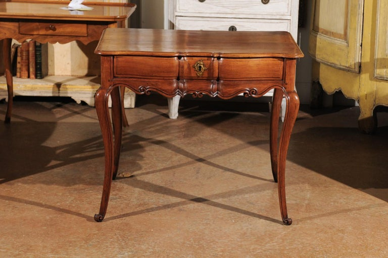 A French Louis XV period fruitwood writing table from the first half of the 18th century, with apron 'en arbalète', single drawer, cabriole legs and original hardware. Born in the southwestern region of France that stretches from Bordeaux to the