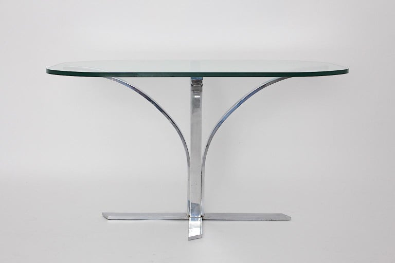 A space age chromed metal vintage dining table or writing table, which was designed and manufactured, 1960s, Germany. The base is a chromed metal construction, which holds a clear glass top with a thickness of 0.80 cm. The design radiates the