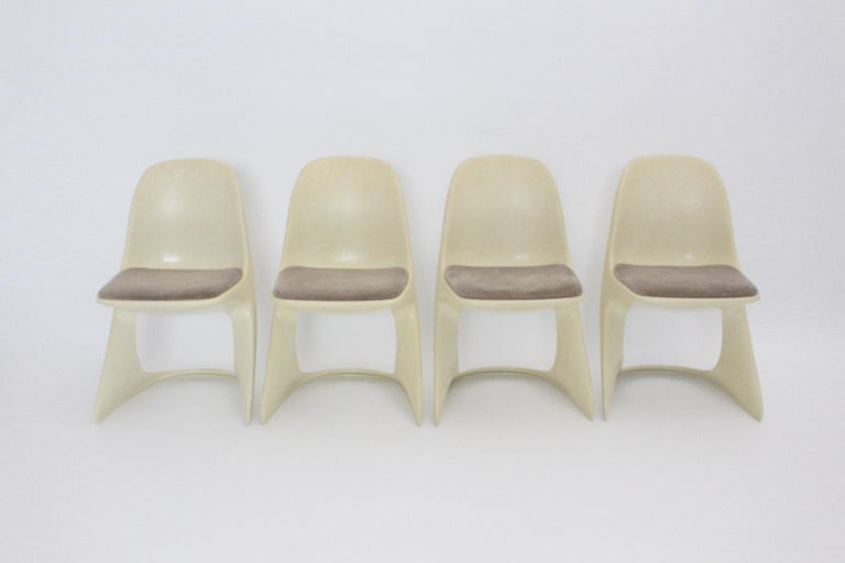 This set of four dining chairs named Casalino by Alexander Begge, Germany, 1971 for Casala, Germany was made of off white plastic. Also the dining chairs feature upholstered seats covered with brown velvet fabric. The vintage condition is very good