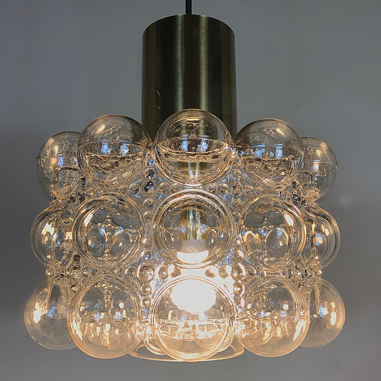 Beautiful Space Age bubble clear glass pendant lamp manufactured by Glashütte Limburg, with the characteristic blown glass designed by Helena Tynell. This lamp is a striking appearance in any room. Due to the sublime combination of glass and brass,