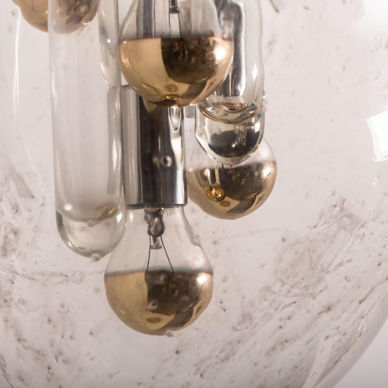 This large hand-blown pendant lamp was made by the German manufacturer Doria in the 1970s. The beautiful handblown glass sphere is mounted on brass colored base.  These high quality light sculpture not only function as light sources but also as a