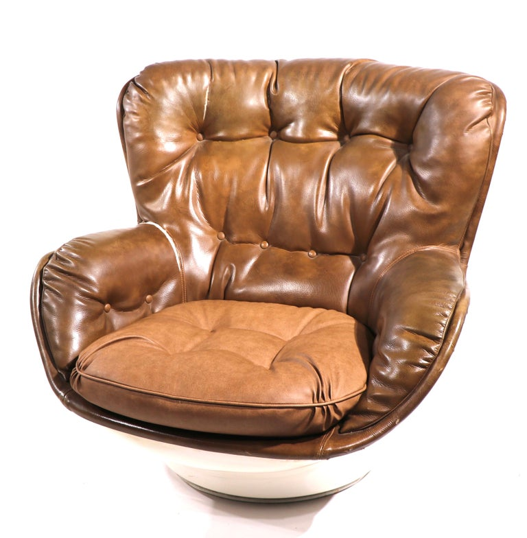 Very cool Space age swivel pod chair, having a white exterior shell, with upholstered interior seat, The white shell is fiberglass, the brown interior is vinyl. The vinyl upholstery has two splits, please see images. The chair is marked Charlton