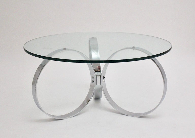 A space age vintage coffee table / sofa table, which shows a chromed base formed with three rings. While a clear glass plate topped the table, the chromed metal base produce a futuristic appearance. In the 1960s people appreciated cool design. It