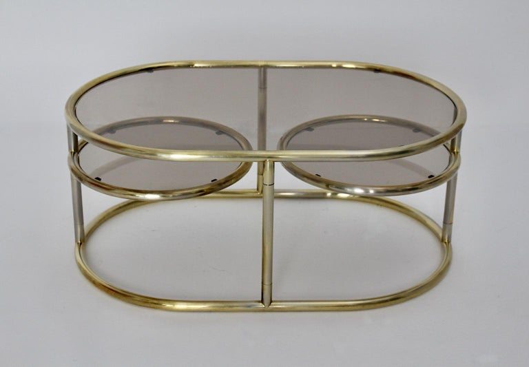 Space Age vintage coffee table or sofa table from golden metal tube frame and glass plates 1960s Italy. While the body of the sofa table shows an oval shaped plate, both revolving plates are round shaped. Gorgeous and useful sofa table in good