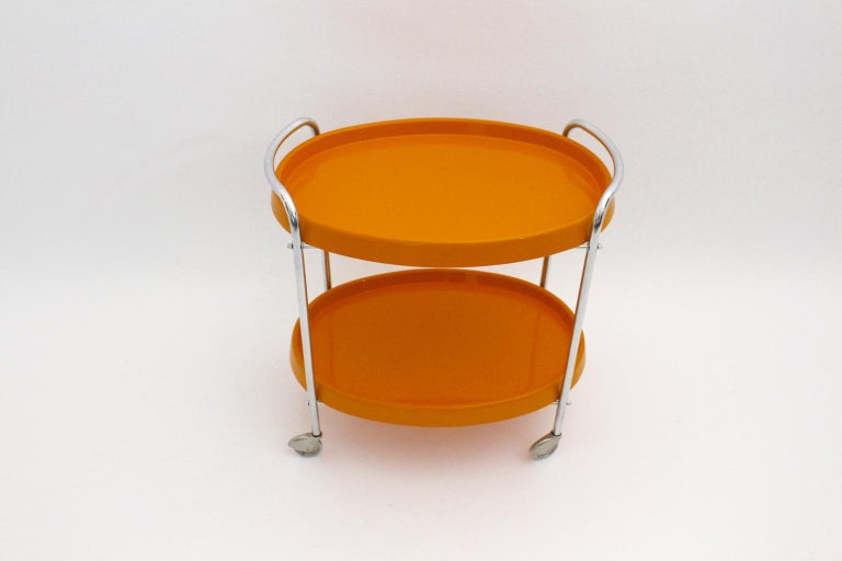 The presented Space Age vintage bar cart from the 1960s shows a chromed tube steel frame and four wheels for mobility. Also the removable orange plastic trays show an oval shape. The vintage condition is very good. Approx. measures: Width 65