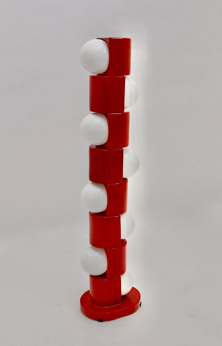 A space age red vintage ceramic totem floor lamp, which was designed and handmade in Italy in the 1960s. The floor lamp was composed of 8 geometric parts, which are round towards the sides, with 8 white glass bulbs (E 27 sockets) and a foot