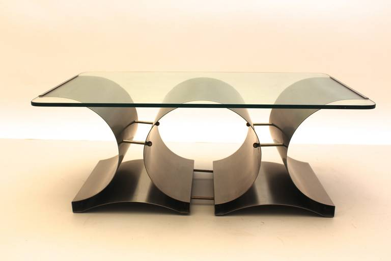 Space Age vintage coffee table or sofa table from stainless steel and clear glass designed by Francois Monnet, France, circa 1970. This sleek and futuristic design shows a stainless steel construction with a clear glass plate, which is fixed on