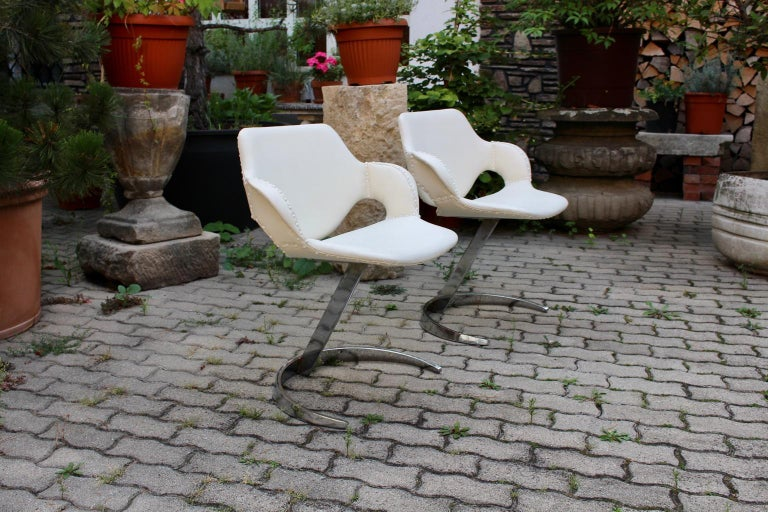 This presented great pair of white faux leather Space Age armchairs, which was designed by Boris Tabacoff, circa 1960, France. The vintage armchairs feature a c-shaped chromed metal base and a white faux leather seat and back. Furthermore the