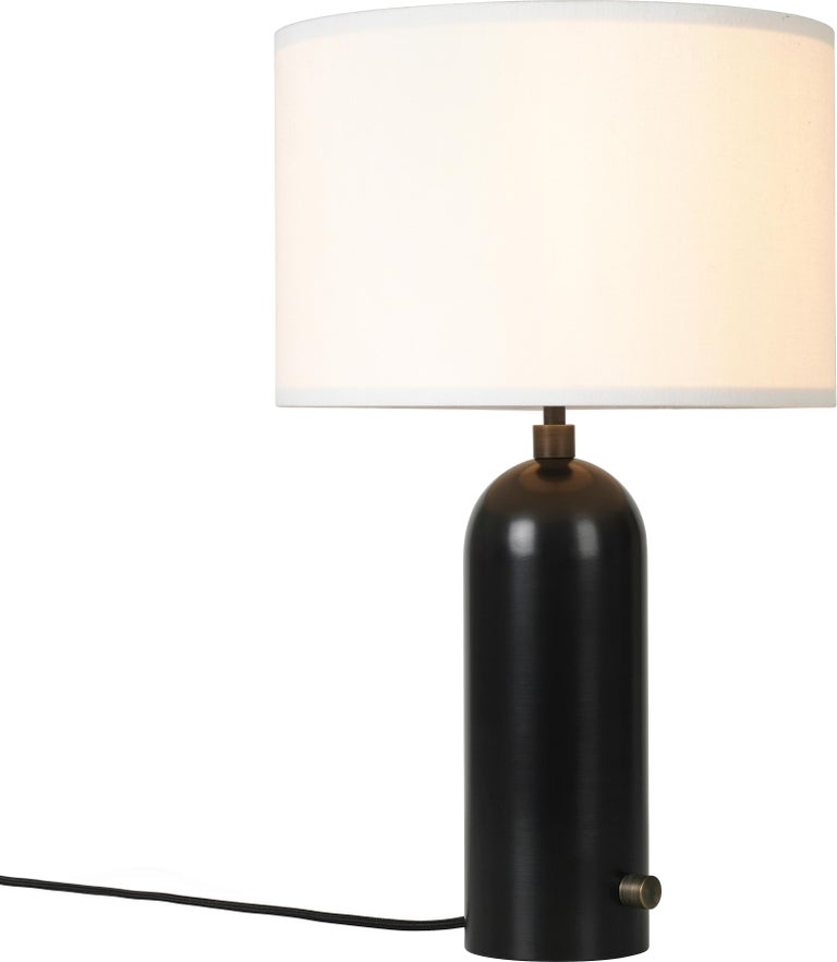 Space Copenhagen 'Gravity' Table Lamp in Blackened Steel for Gubi. Executed in blackened steel with a white textile (or canvas) shade, antiqued brass dimmer in bass and black cloth cord. Taking its name from the lamp's distinctive balance between