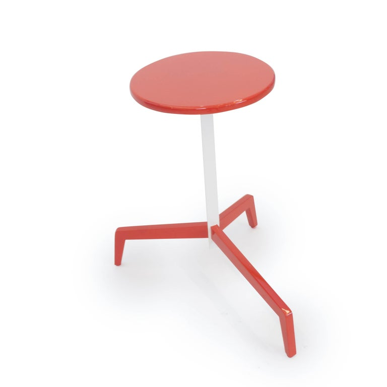 This red and white lacquered side table is conveniently designed to fit in any room. The long protruding leg slides under tables and benches to maximize your space. This table can be sold as is or custom made in any color of the customers' choosing.