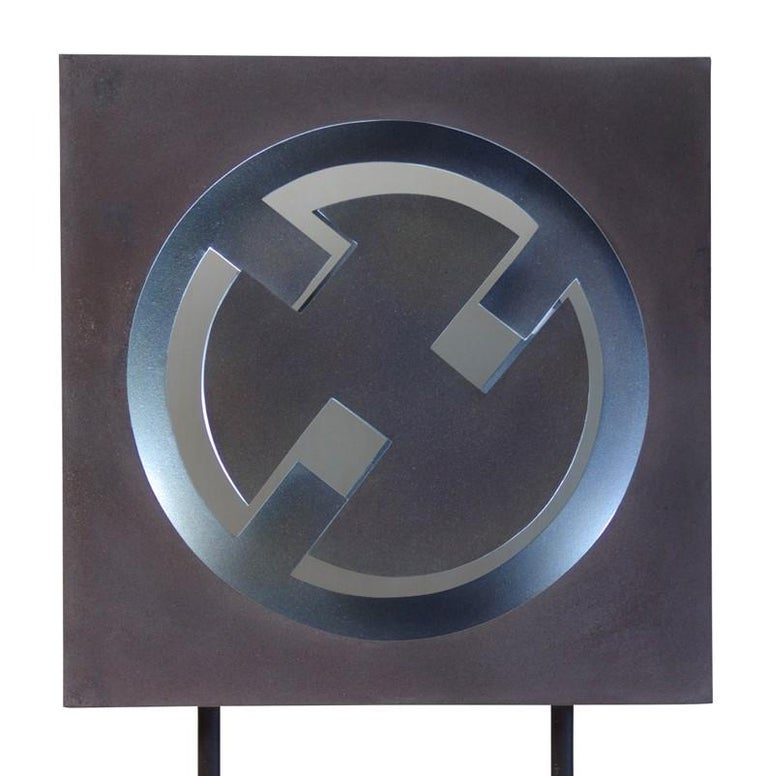 The striking dynamism of this unique sculpture is the result of the clever use of materials to create a captivating piece that is not only a contemporary artwork but also a source of light. A dark grey background frames a metallic ring with three
