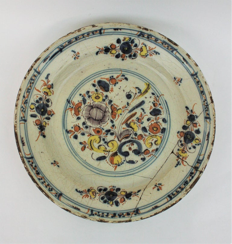 Spanish Faience charger with floral motifs. Talavera de la Reina-Puente del Arzobispo, Toledo. Spain, late 17th century. Hand painted in ochre, yellow, brown and blue with a central roundel with a floral bouquet. Four smaller bouquets with stylised