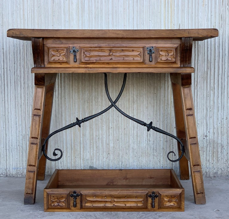 A Spanish walnut side table with single drawer, scalloped apron, carved legs and iron side stretcher from the late 19th century.  The front it´s the same that the back, you can see in picture 2.  This elegant Spanish table features a simple,