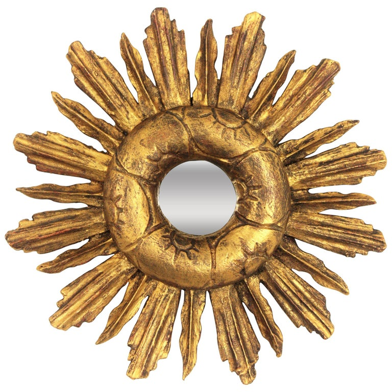 Unusual Baroque style small sized carved giltwood sunburst mirror with a decoration of carved suns at the frame surrounding the glass. Spain, 1940-1950. It has an interesting aged patina and it is a beautiful mirror to place it with other sunburst