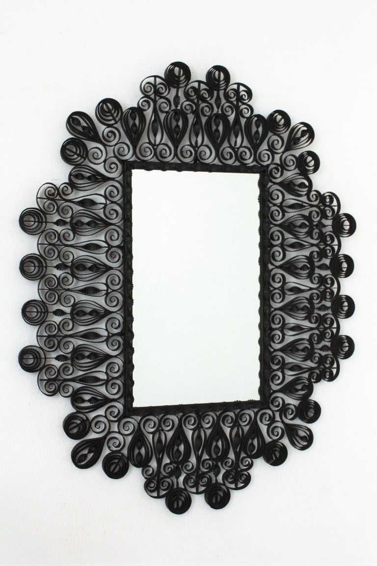 Impressive ornamented scrolled and twisted wrought iron rectangular mirror with Gothic style accents. Spain, 1940s. This handcrafted mirror was manufactured in Spain at the Mid-Century Modern period. The frame is heavily decorated with