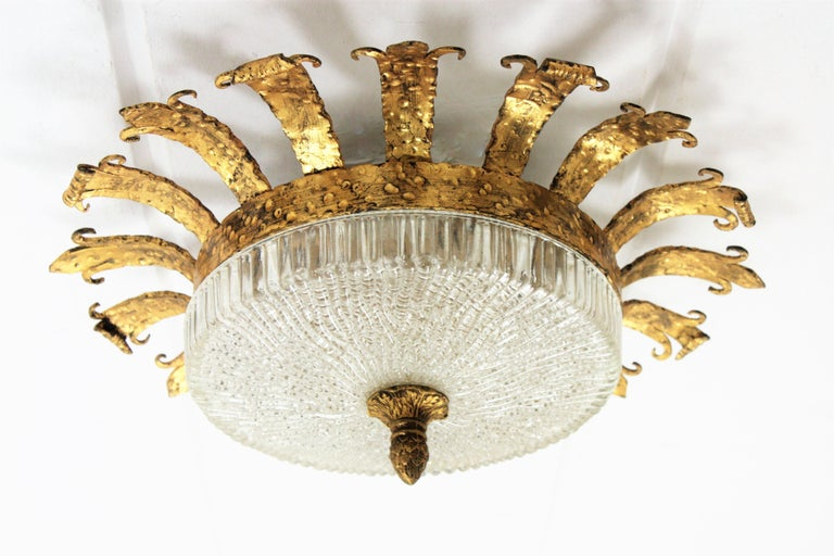 An sculptural hand-hammered iron and glass ceiling light fixture with neoclassical and Gothic Revival accents. A forged and gilded iron fixture with a fluted frosted glass shade with a gilt iron ornamented finial. This lamp has an highly decorative