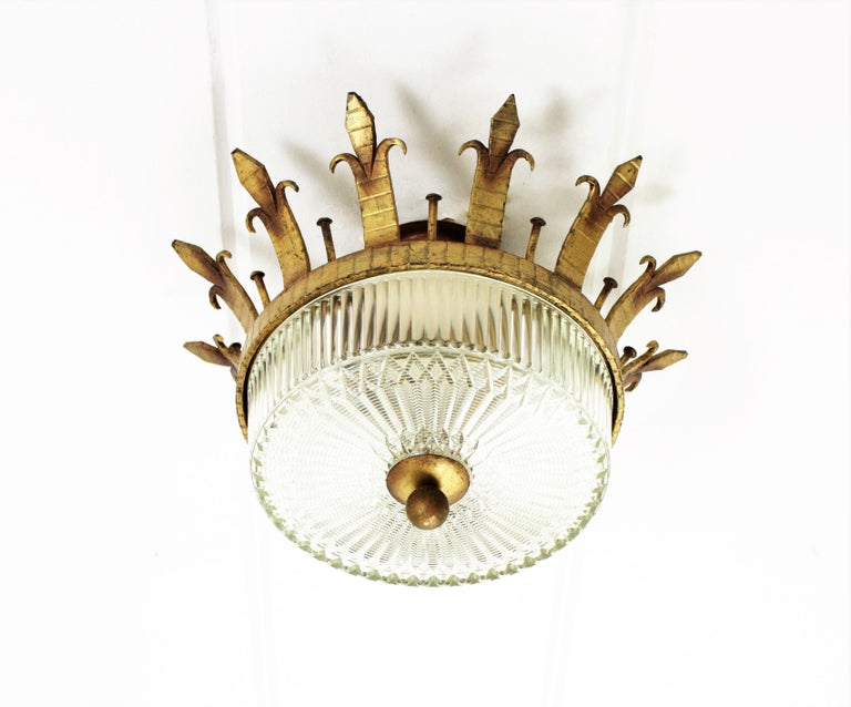 An sculptural hand hammered iron and glass ceiling light fixture with neoclassical and gothic revival accents. Spain, 1930-1940s. A forged and gilded iron flush mount with canopy, a fluted frosted glass shade and a gilt iron ball finial. This lamp