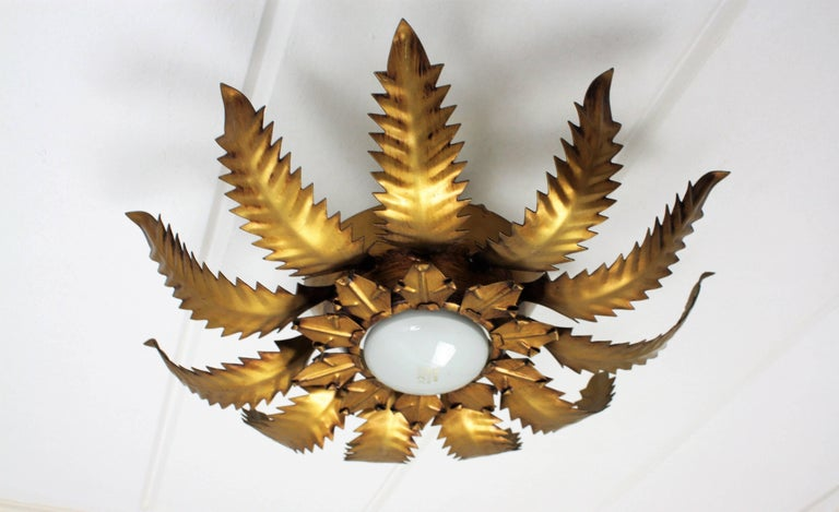 A beautiful hand-hammered two tires gilt iron ceiling light fixture with leaves in two sizes. Spain, 1950s. The metal leaves with its scalloped cut design highlight this flush mount. This piece is in excellent vintage condition and it has a lovely