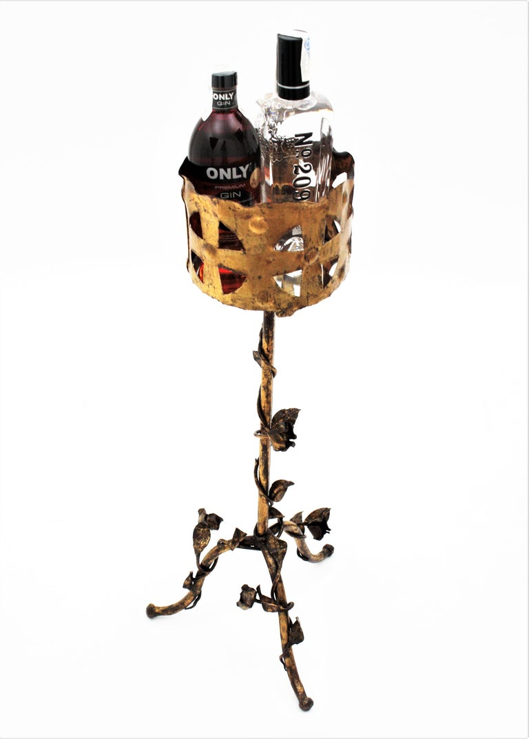 A beautiful hand-hammered gilt iron pedestal richly decorated with leaves, roses and gold leaf gilt finishing, Spain, 1950s. It has Gothic style and Art Nouveau accents. The top has cut and hammered decorations and stands on a tripod base finely