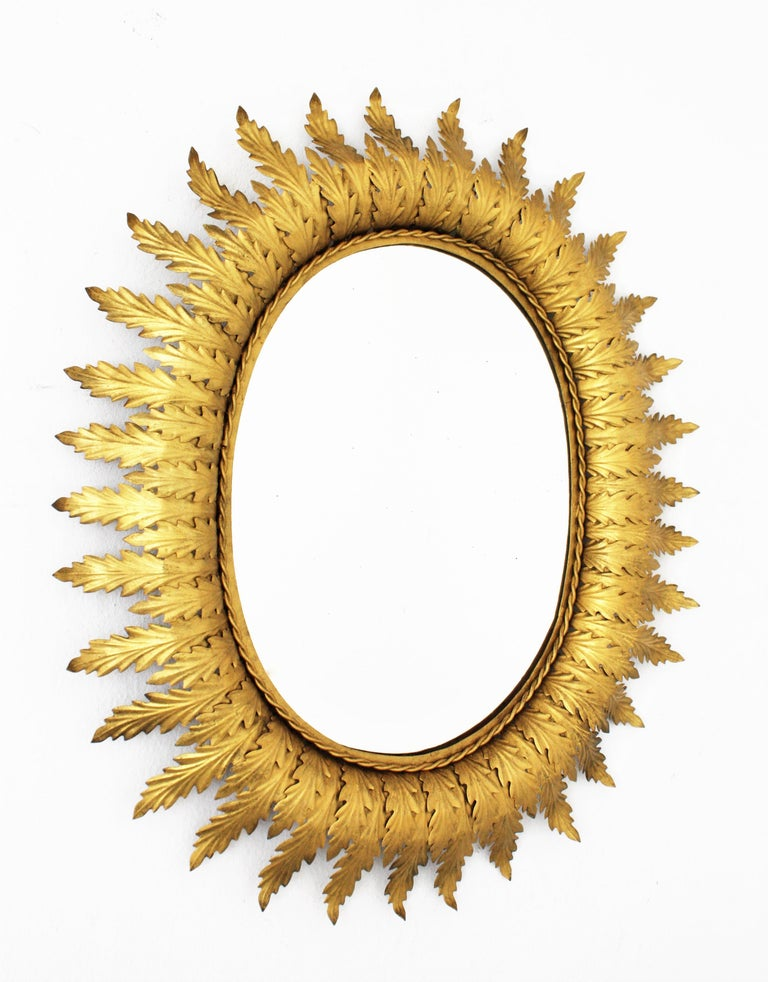 Lovely gilt metal oval shaped sunburst mirror in the Hollywood Regency style. The frame is comprised of a series of overlaying leaves in two sizes. Beautiful to place in a powder room or over a dressing table, Spain, 1950s. Overall measurements: H