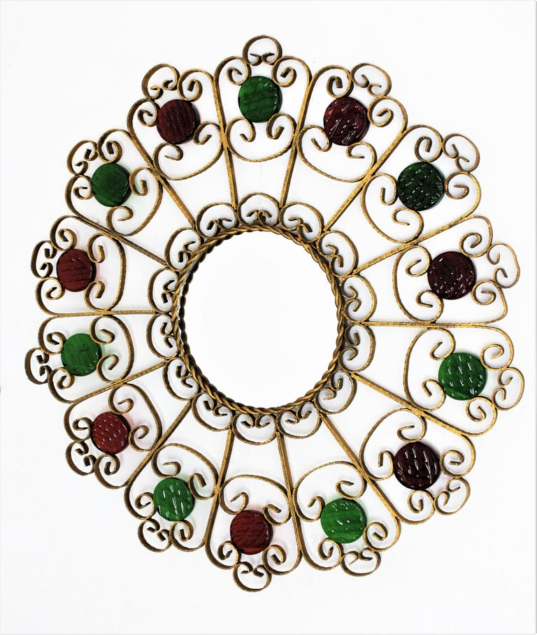Beautiful wrought gilt iron flower burst / sunburst scroll motif mirror framed with garnet and green glasses, Spain, 1950s.