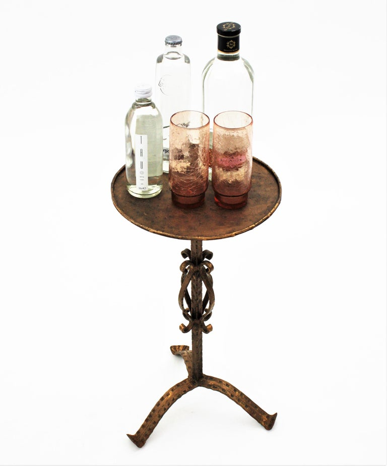 Lovely hand-hammered iron Guéridon / end or side table with bronze-gilt patina and ornamented base. Spain, 1950s-1960s. The round top stands on a tripod base ornamented with scroll motifs. The feet of this Martini table are richly decorated by