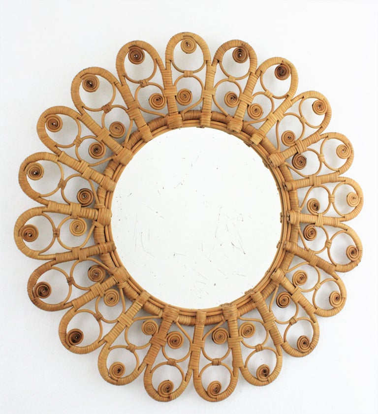 Eye-catching handcrafted wicker sunburst / flower shaped mirror with artistic peacock filigree frame. Spain, 1960s. This mirror has all the taste of the Mediterranean and Bohemian style. Manufactured in wicker and rattan with natural finish without