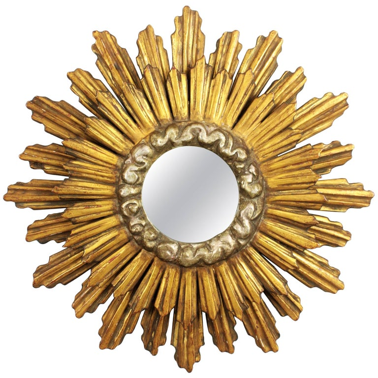 A magnificent wood carved silvered and giltwood double layered sunburst mirror in Baroque style. Spain, 1930s. The frame is finished with gesso and gold leaf gilt and a the central part surrounding the glass is finished with silver leaf. It retains