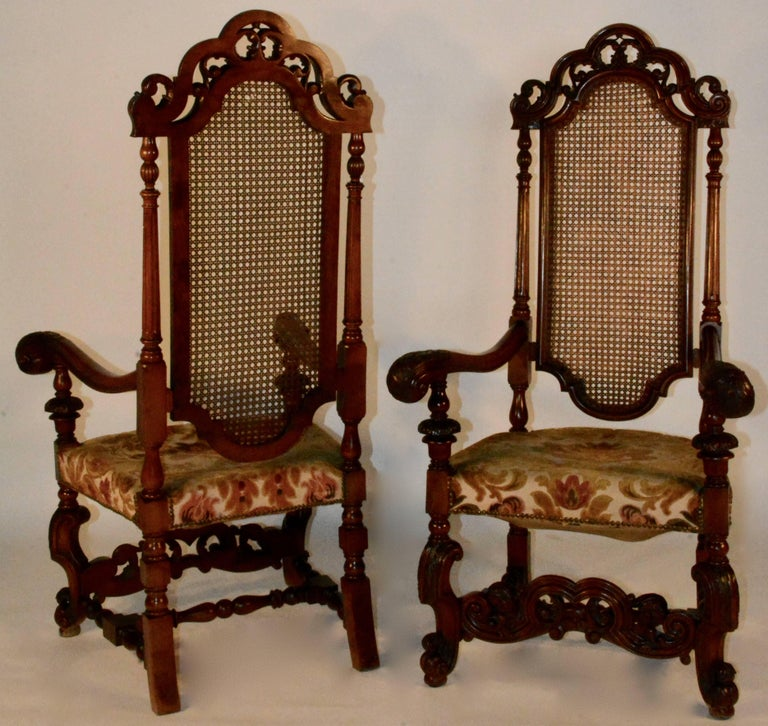 Spanish Baroque high back chairs with scalloped top rail with a pierced scroll carved crest. Curved arms with a highly carved knuckle and a multi-color upholstered seat. A stretcher at the bottom front has complementary scrollwork and piercing that