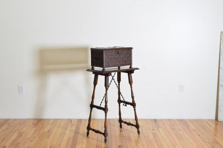 The box with intricate applied carvings and a gadrooned carved molded edge with iron hinges and a centered medallion raised on round flattened disk feet, the tall stand with turned legs joined by wooden and iron stretchers, first quarter of the 20th