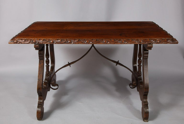 Fine 18th century Spanish baroque trestle table, the two plank top with foliate scroll carved edge, the shaped trestle ends with central turned column, and having original scrolled wrought iron stretchers, the whole possessing good rich color and