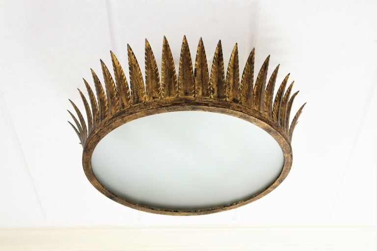 Hand-hammered gilt iron sunburst crown light fixture with frosted glass difussor. Manufactured by Ferro-Art. Spain, 1950s. This gorgeous large crown light fixture was handcrafted in Spain at the Mid-Century Modern period with Brutalist style