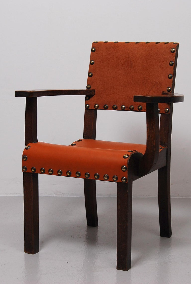 A spanish colonial massive wooden chair with broad, curved armrests and with new, thick leather seat and back. Good condition.