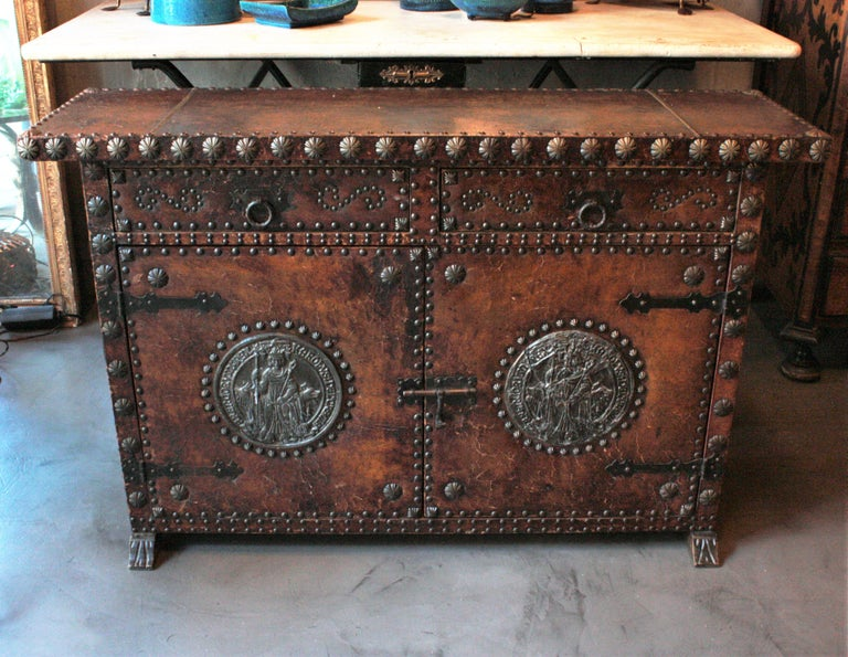 Terrific traditional leather and wood cabinet or sideboard with studwork and decorative panels, Spain, 1940s. This handsome cabinet has two drawers over two doors. It is upholstered in brown leather which is decorated with large silvered studs and