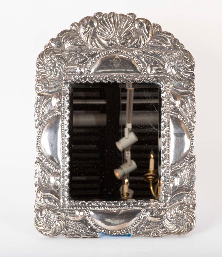 A Peruvian silver repousse picture frame or table top mirror. Hand worked in the Spanish Colonial style decorated in floral and shell motifs. This is a wonderful looking and distinct vanity mirror that will also make a great frame for that favorite