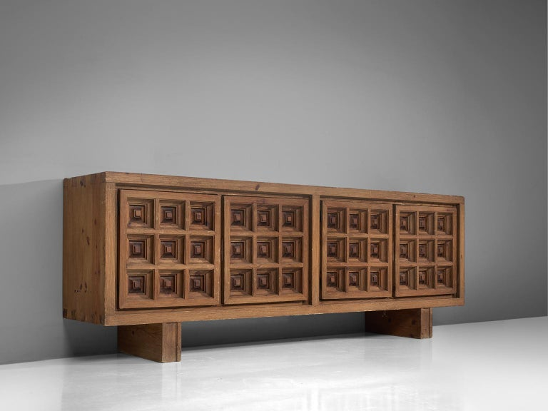 Biosca, sideboard, stained pine, Spain, 1960s.  Outstanding Spanish sideboard that is executed by Biosca in a beautiful way. The four-door credenza features doors with a graphic carved pattern. This is very typical for Brutalist style, while the