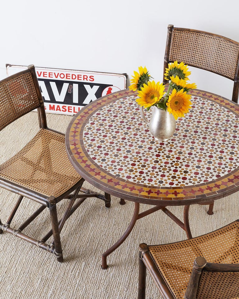Fantastic Spanish dining table or garden table featuring a round stone top with Moroccan mosaic tile inlay. The intricately detailed tiles consists of octagonal shaped stars surrounded by squares. The border of the table has a darker band with red