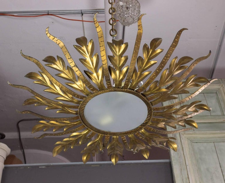 Gilt metal ceiling fixture with frosted glass and two candelabra bulb sockets (Max 40 watt bulbs.) Hand-hammered detailing around glass border and leaves. This fixture has recently been UL wired and is sold with a canopy and chain.