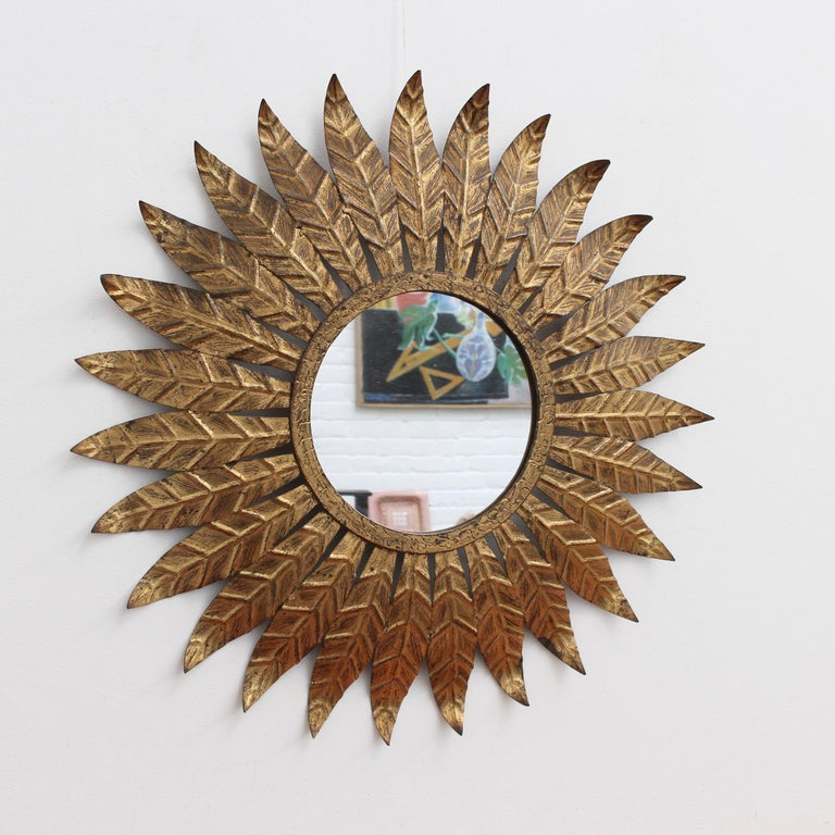Spanish gilt metal sunburst mirror (circa 1960s) with leaf motif rays emanating from the glass border. In fair vintage condition commensurate with age and use. Some authentic age spots and characterful markings appear on gilt surface adding