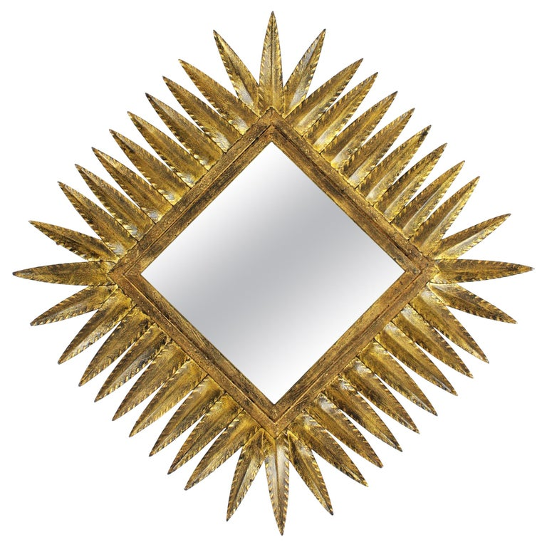 Hand-Hammered Gilt Iron Rhombus shaped sunburst mirror. Spain, 1950s.  It can be placed in two positions.  Manufactured by Ferro Art.  Dimensions in rhombus shape: 69cm H x 68cm W. Dimensions in square shape: 57 cm H x 57cm W.