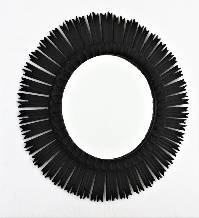 Large carved black painted sunburst mirror in the style of Baroque, Spain, 1940s. This wooden sunburst mirror has been finished in a black patina to add a modern taste. The dark color gives a theatral appearance to this Baroque style wall