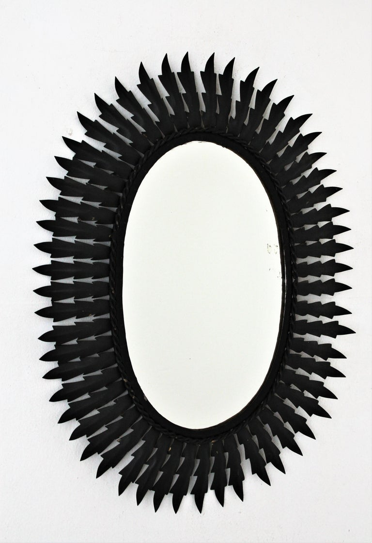 An eye-catching oval sunburst mirror handcrafted in metal with black matte painted finishing. Spain, 1960s.